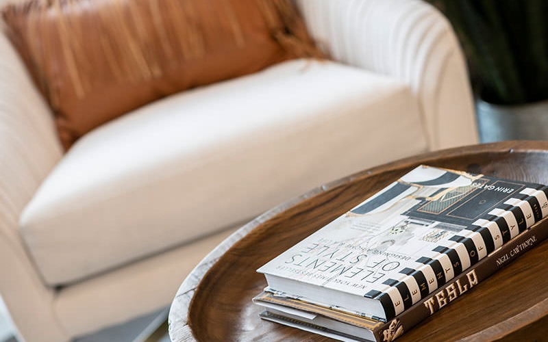 a comfy chair and books on a table representing designer influenced lifestyle