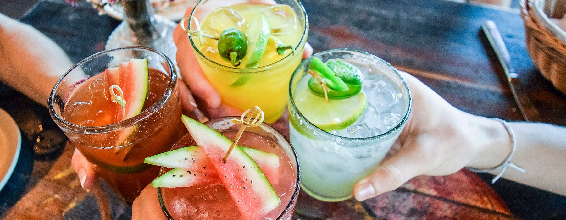 lifestyle image of s group of hands clicking their margaritas together